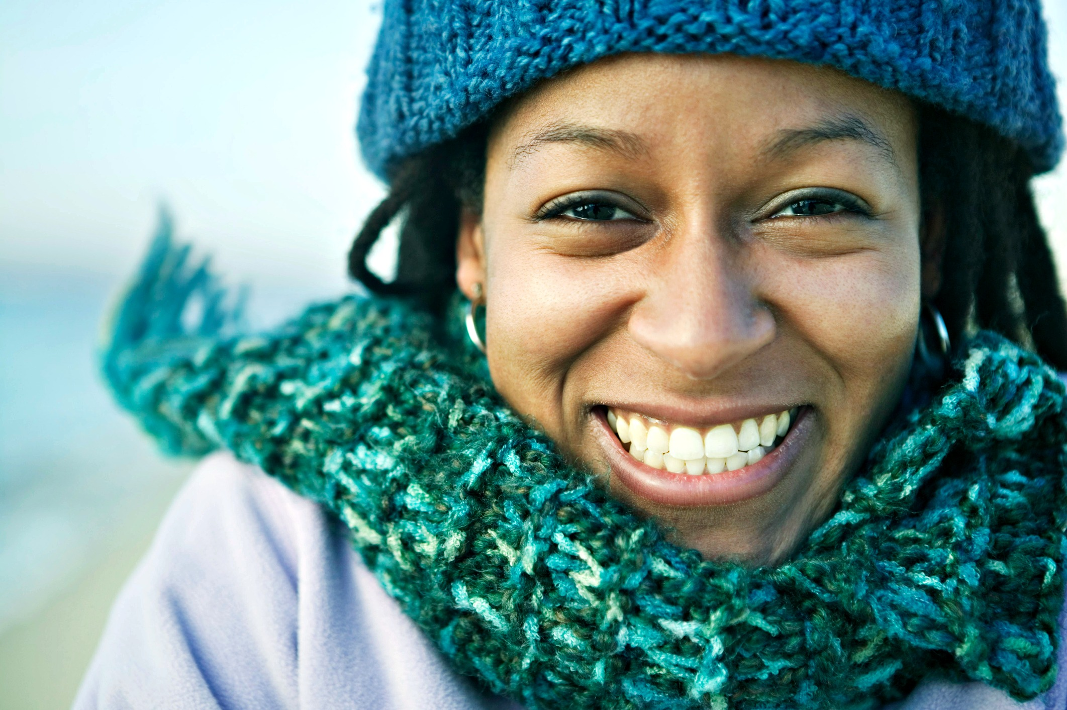 Headshot of a smiling face woman of color feeling good. She's wearing a blue knitted winter hat and a sea-green knitted scarf while outside. Counseling creates possibility.