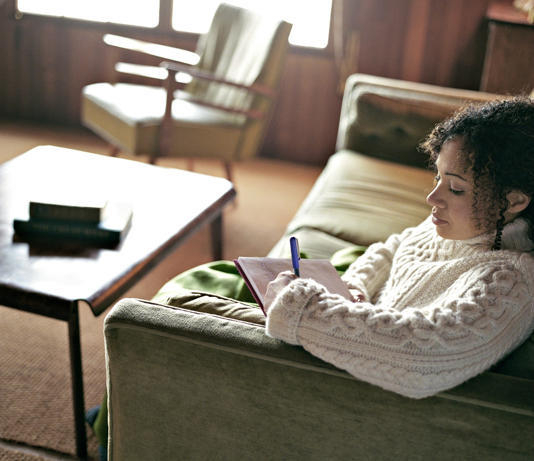 Woman sitting on couch writing self-reflections about her psychotherapy and counseling session.